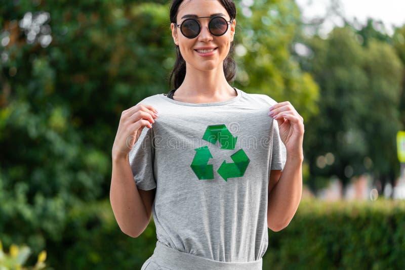 Młoda uśmiechnięta atrakcyjna kobieta w szarej koszulce z przetwarza symbol w parku zdjęcia royalty free