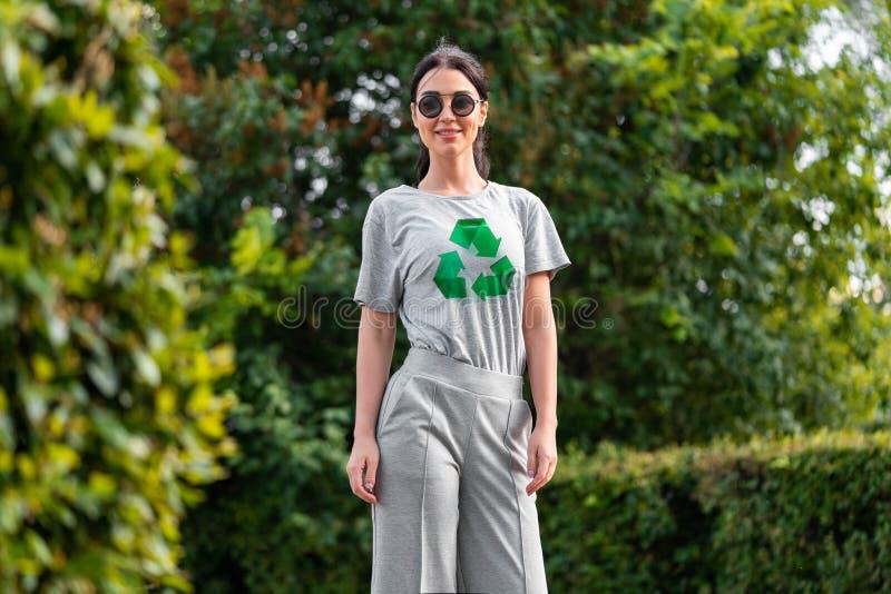 Młoda uśmiechnięta atrakcyjna kobieta w szarej koszulce z przetwarza symbol w parku fotografia stock