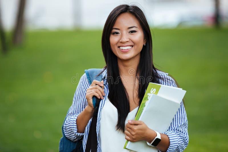 Młoda uśmiechnięta azjatykcia studencka kobieta z plecakiem, trzyma noteboo zdjęcie stock