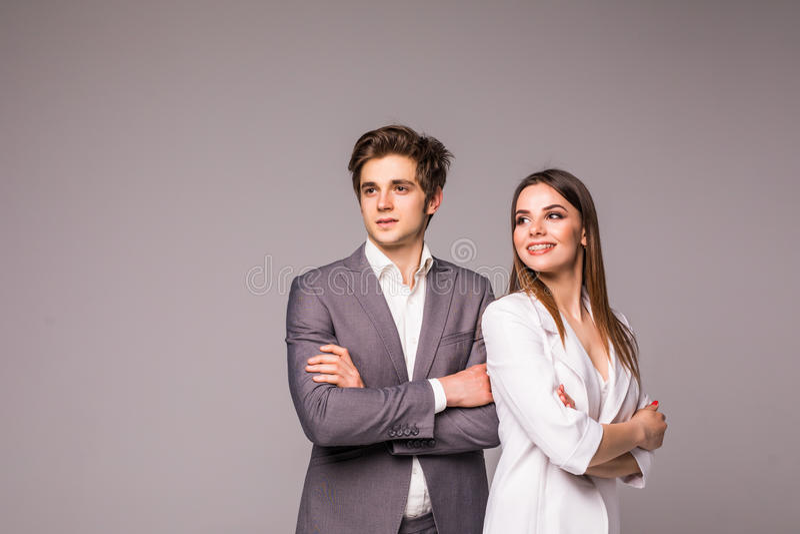 Młoda uśmiechnięta biznesowa kobieta i biznesowy mężczyzna odizolowywający na szarym tle obrazy royalty free