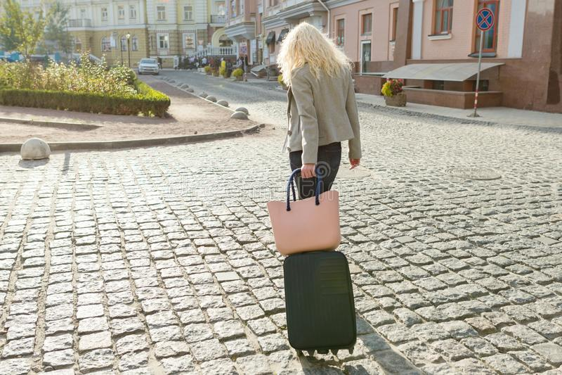 Młoda uśmiechnięta blond kobieta z podróż telefonu i torby odprowadzeniem przy miasto ulicą, kobieta z okularami przeciwsłoneczny fotografia royalty free