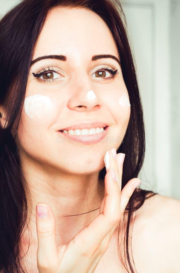 Młoda uśmiechnięta caucasian dziewczyna używa wiek twarzy śmietankę obrazy royalty free