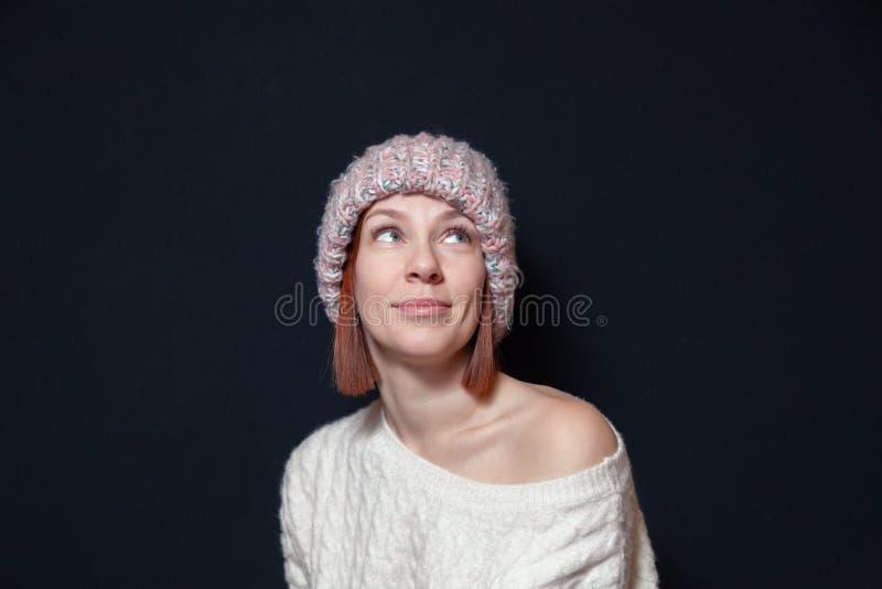 Młoda uśmiechnięta czerwona z włosami dziewczyna z koczka ostrzyżeniem w różowym kapeluszu, trykotowy beżowy pulower na białym tl zdjęcia stock