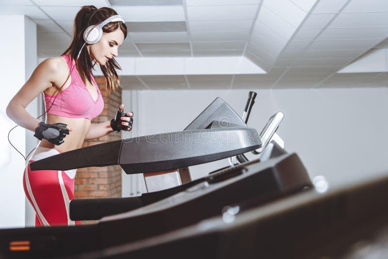 Młoda uśmiechnięta dziewczyna biega na karuzeli w sporta klubie z hełmofonami Pojęcie sporta i aktywnego style życia fotografia royalty free