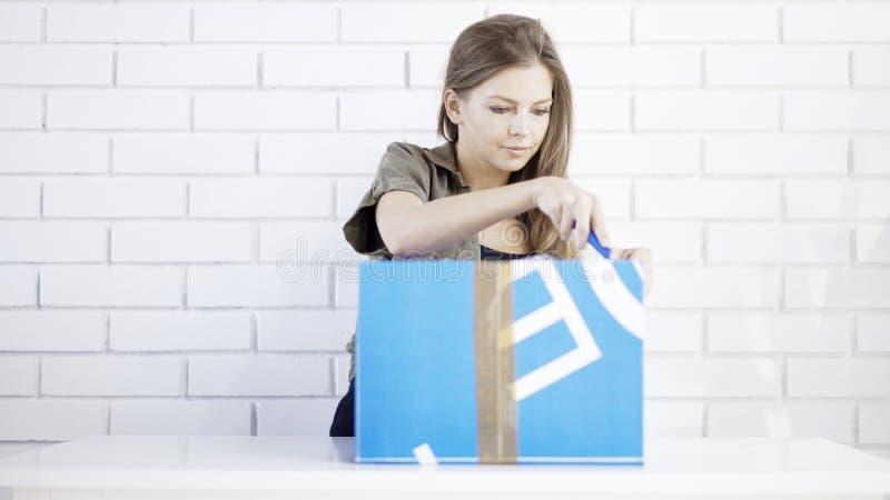 Młoda uśmiechnięta dziewczyna otwierał pudełkowatego prezent zdjęcie stock