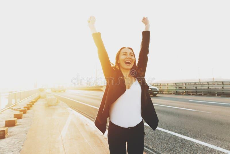 Młoda uśmiechnięta dziewczyna raduje się trzymający jej ręki w górę obraz stock