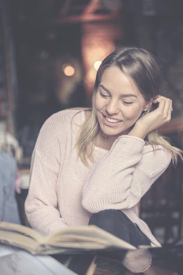 Młoda uśmiechnięta dziewczyna ucznia czytelnicza książka w domu fotografia stock