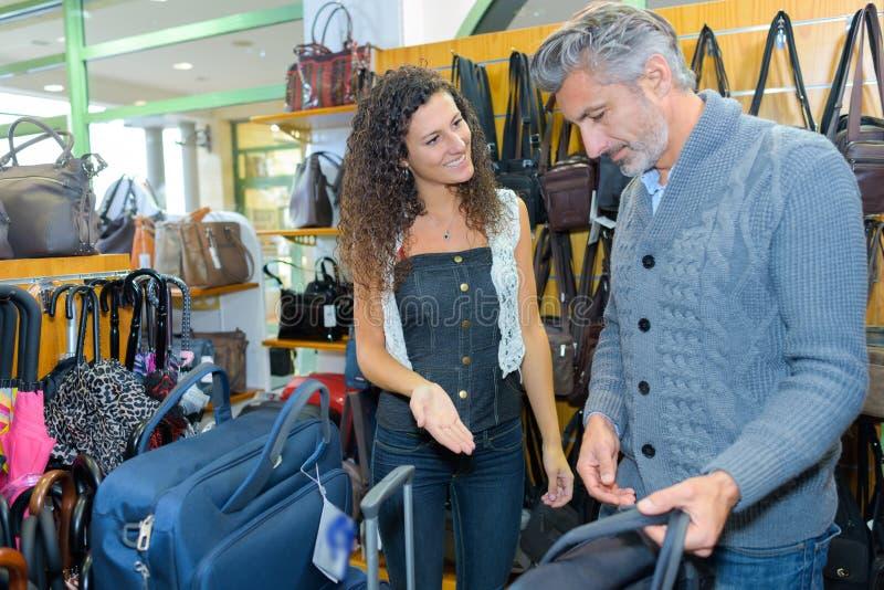 Młoda uśmiechnięta dziewczyny kupienia walizka fotografia stock