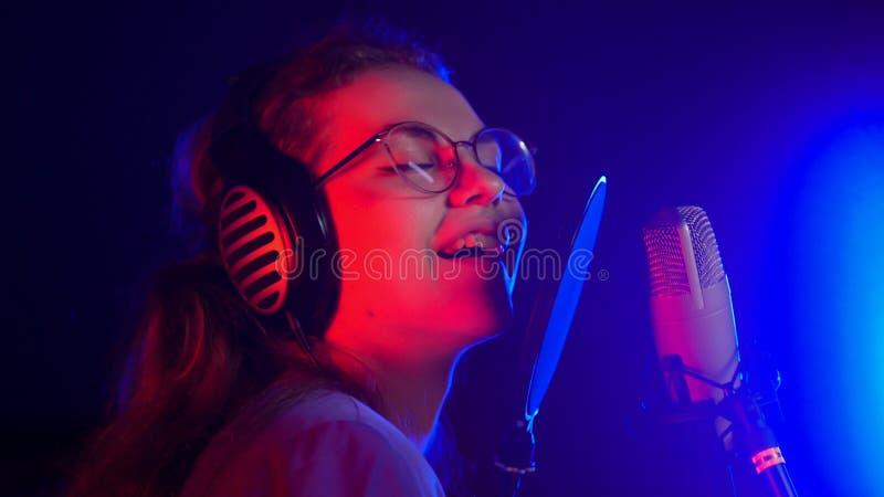 Młoda uśmiechnięta emocjonalna kobieta śpiewa w neonowym oświetleniu w studiu w szkłach zdjęcia royalty free
