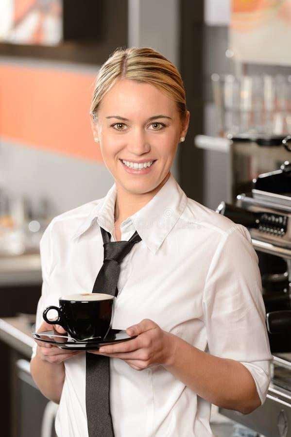 Młoda uśmiechnięta kelnerka z filiżanką kawy obraz royalty free
