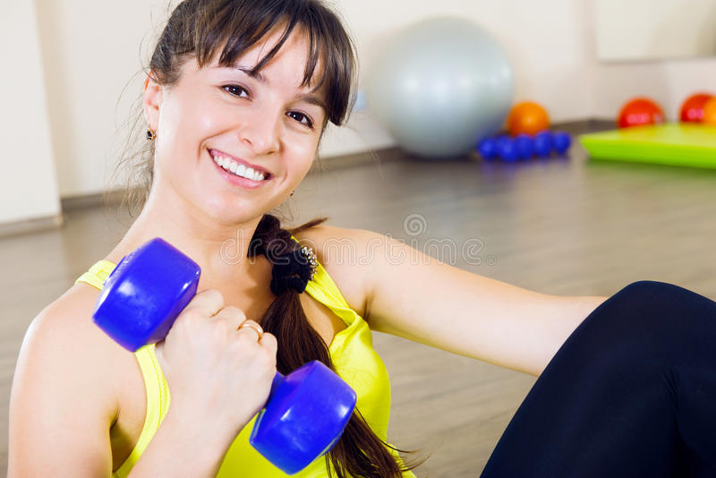 Młoda uśmiechnięta kobieta ćwiczy z dumbbells obrazy stock