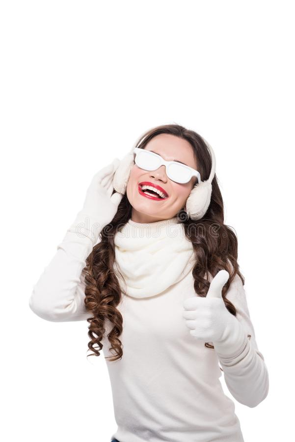 młoda uśmiechnięta kobieta jest ubranym białych nieprzezroczystych okulary przeciwsłonecznych i pokazuje kciuk up w zima ubiorze, zdjęcie royalty free