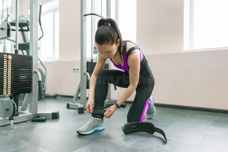 Młoda uśmiechnięta kobieta jest ubranym rzemienne kostek patki przygotowywa ćwiczyć na sprawności fizycznej maszynie w gym sprawn obrazy royalty free