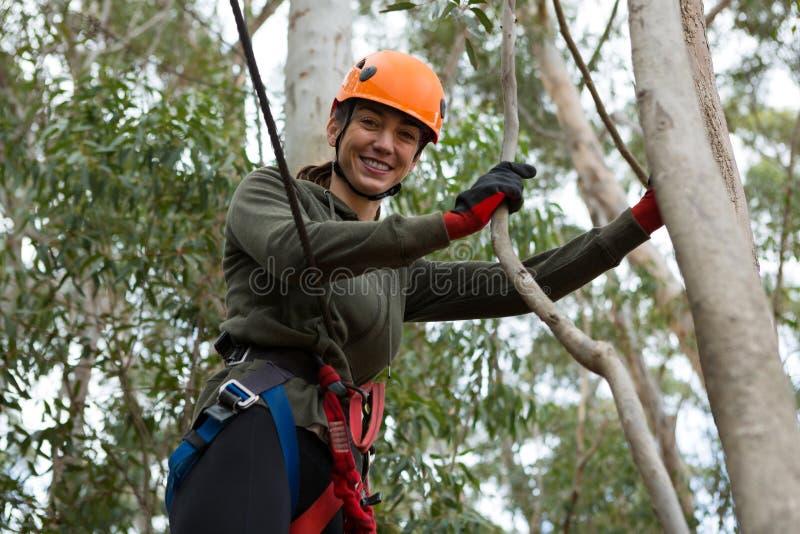 Młoda uśmiechnięta kobieta jest ubranym zbawczego hełm opiera na gałąź w lesie obrazy royalty free
