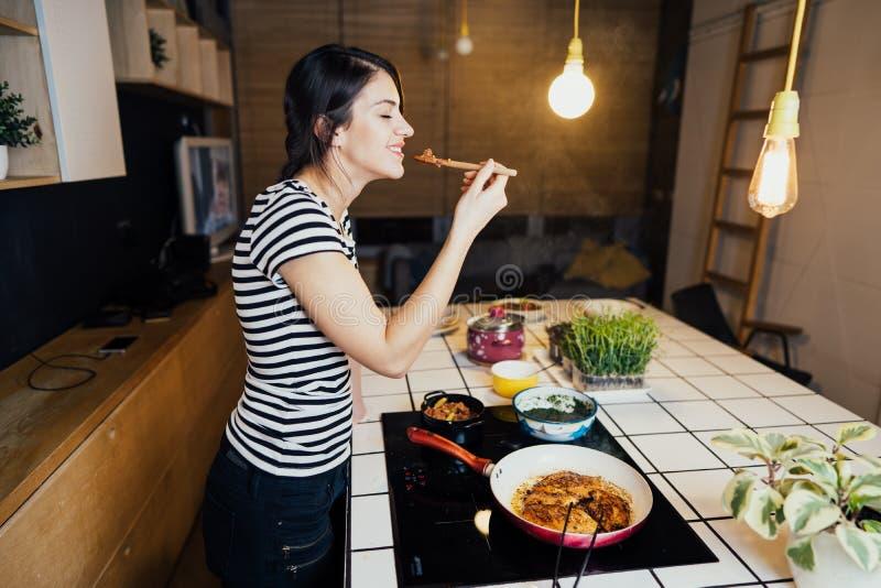 Młoda uśmiechnięta kobieta kosztuje zdrowego keto posiłek w domowej kuchni Robić gościowi restauracji stoi bezczynnie indukcji ho obrazy stock