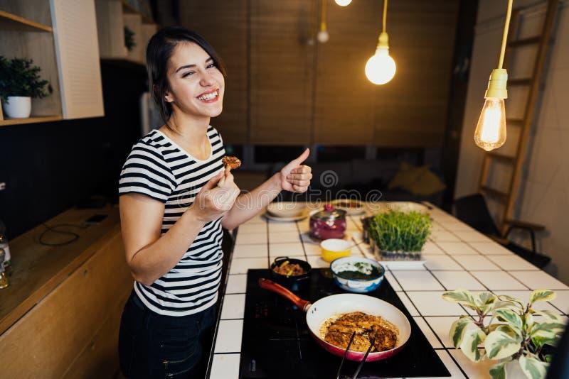 Młoda uśmiechnięta kobieta kosztuje zdrowego posiłek w domowej kuchni Robić gościowi restauracji stoi bezczynnie indukcji hob na  fotografia stock