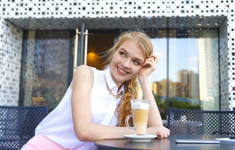 Młoda uśmiechnięta kobieta ma kawowej przerwy obsiadanie przy kawiarnią i pije latte przez słomy Modny blond europejski dziewczyn obrazy stock