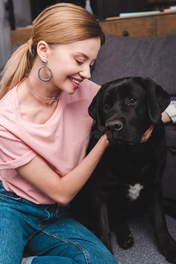 młoda uśmiechnięta kobieta obejmuje czarnego labradora na kanapie obrazy stock