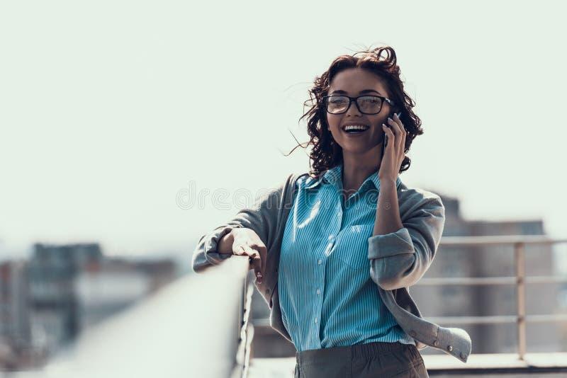 Młoda Uśmiechnięta kobieta Opowiada na telefonie komórkowym Plenerowym zdjęcia stock