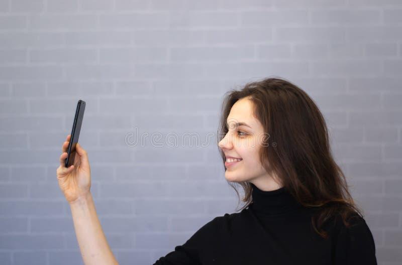 Młoda uśmiechnięta kobieta przez kamer spojrzeń przy jej pojawieniem obrazy stock