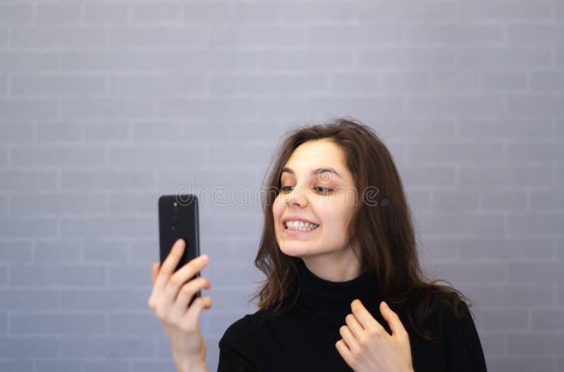 Młoda uśmiechnięta kobieta przez kamer spojrzeń przy jej zębami zdjęcie stock