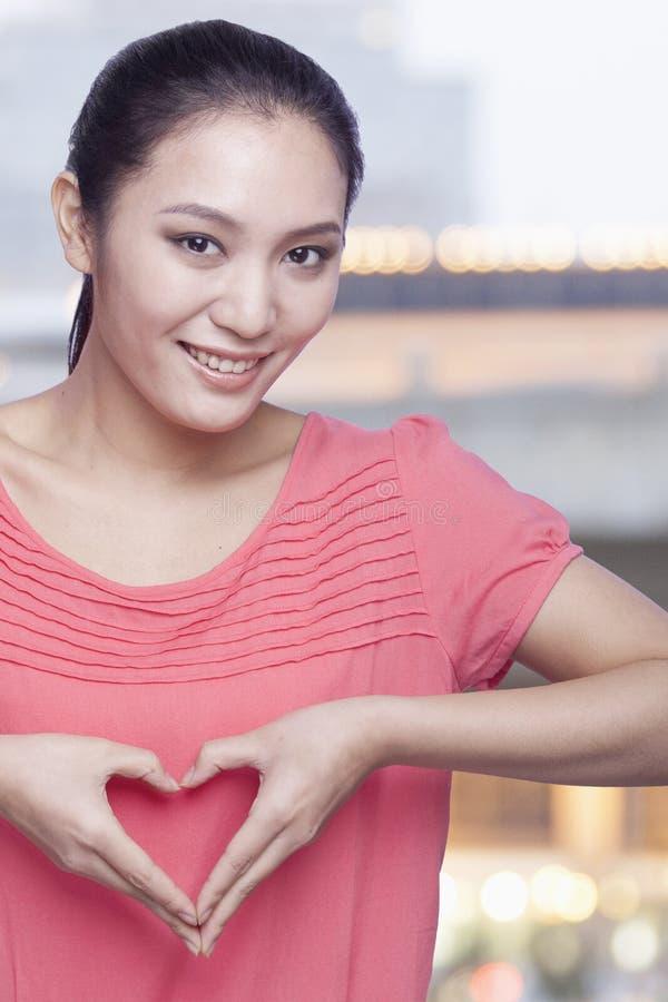 młoda uśmiechnięta kobieta robi sercu podpisywać z rękami i patrzeje kamerę zdjęcia royalty free