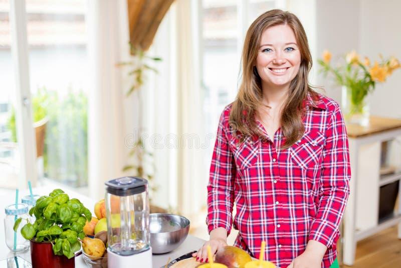 Młoda uśmiechnięta kobieta robi smoothie z świeżymi zieleniami w blender w kuchni w domu zdjęcia stock