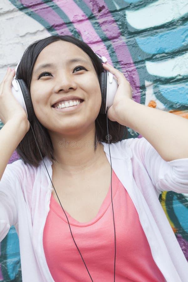 Młoda uśmiechnięta kobieta trzyma jej hełmofony podczas gdy cieszący się słuchać muzyka przed ścianą z graffiti obrazy stock