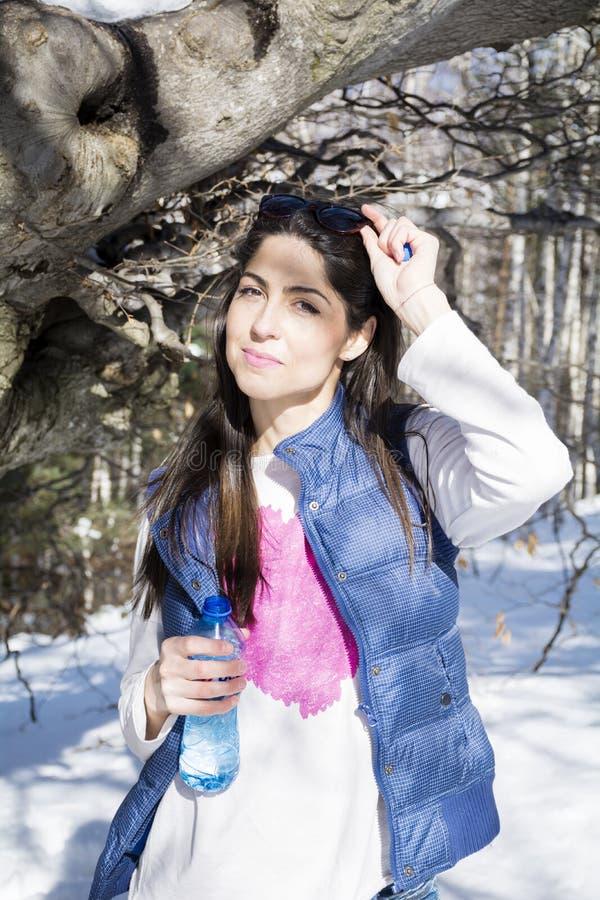 Młoda uśmiechnięta kobieta w zimy góry wodzie pitnej zdjęcia royalty free