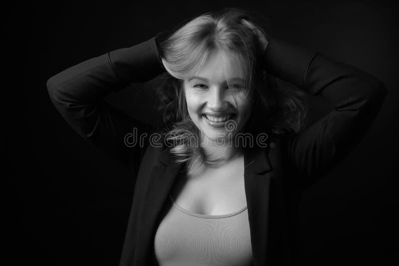 Młoda uśmiechnięta kobieta z naturalnym makijażem w czarnej kurtce fotografia stock
