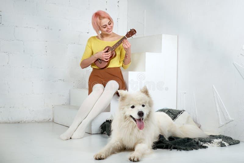 Młoda uśmiechnięta kobiety dziewczyna w spódnicie i bluzce, bawić się ukulele, siedzi na krokach z uśmiechem na jej twarzy obraz stock
