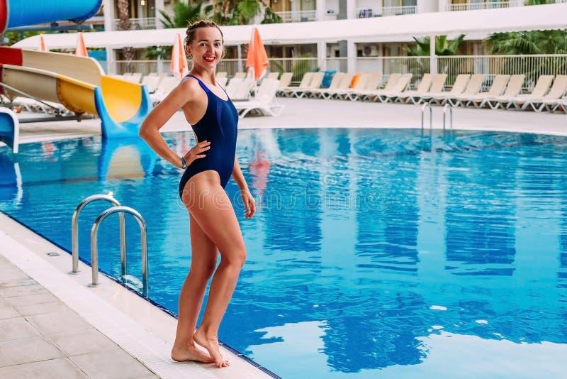 Młoda uśmiechnięta nikła kobieta w zmroku - błękitny sporta swimsuit stoi bezczynnie plenerowego basenu w hotelu w lecie Kobieta  obraz royalty free