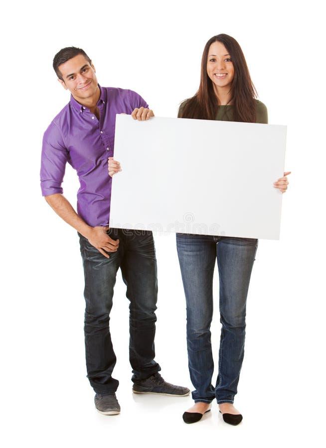 Młoda Uśmiechnięta para Podtrzymywał puste miejsce znaka obrazy stock