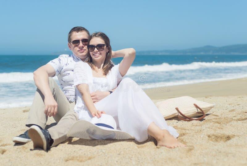 Młoda uśmiechnięta para siedzi na plaży w okularach przeciwsłonecznych obrazy stock