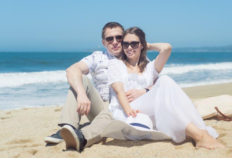 Młoda uśmiechnięta para siedzi na plaży w okularach przeciwsłonecznych zdjęcie royalty free