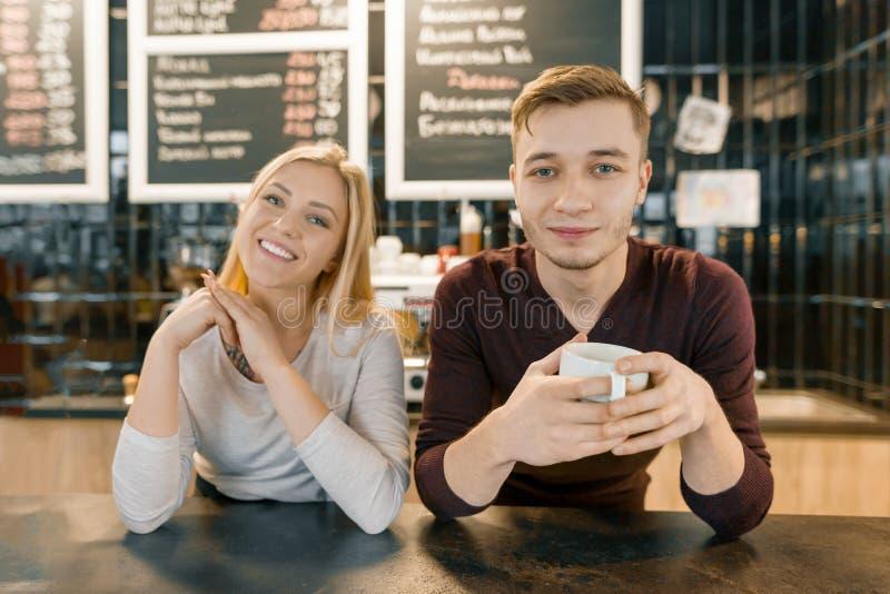 Młoda uśmiechnięta para sklepów z kawą pracownicy, mężczyzna i kobieta pozuje blisko, zakazujemy odpierającą i kawową maszynę z f zdjęcia stock