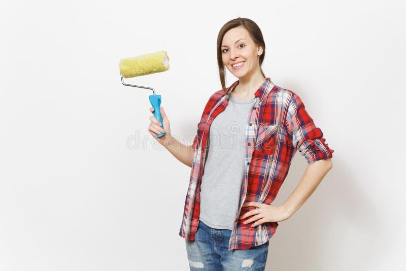 Młoda uśmiechnięta piękna kobieta trzyma farba rolownika dla ściennego obrazu odizolowywającego na białym tle w przypadkowych ubr fotografia royalty free