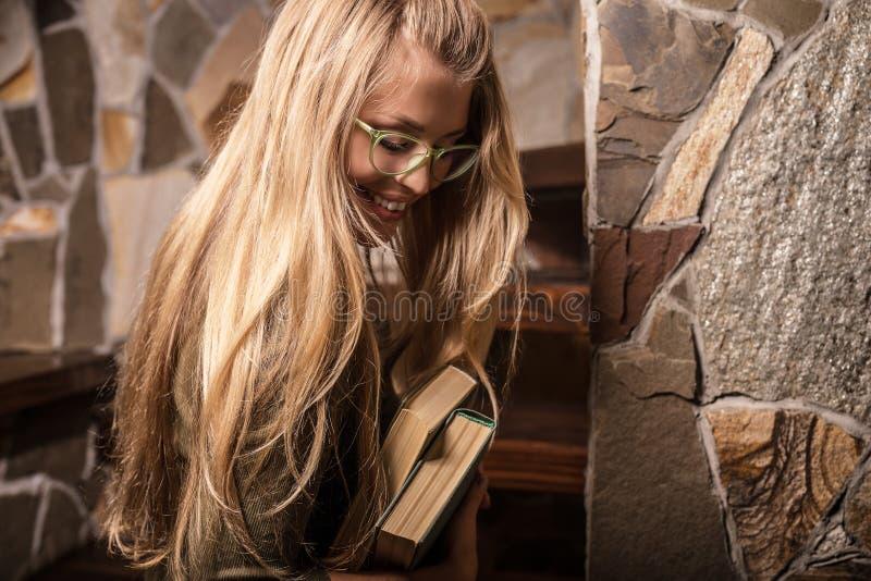 Młoda uśmiechnięta piękno kobieta przeciw domowemu wnętrzu z książkami obraz royalty free