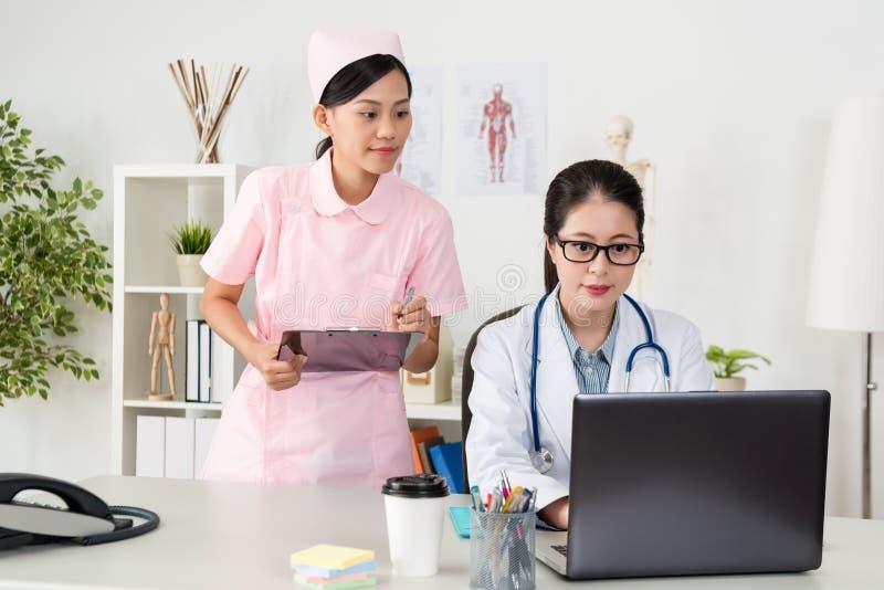 Młoda uśmiechnięta pielęgniarka używa schowka writing notatkę obraz stock