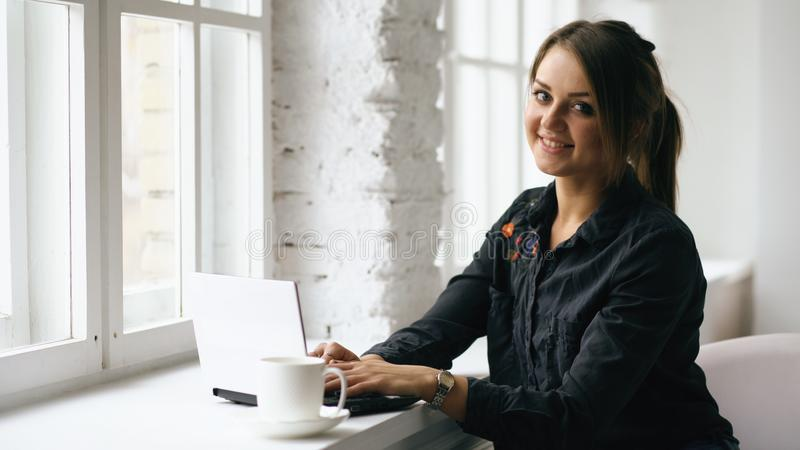 Młoda uśmiechnięta studencka kobieta siedzi w sklep z kawą przy stołem z laptopem indoors obraz royalty free