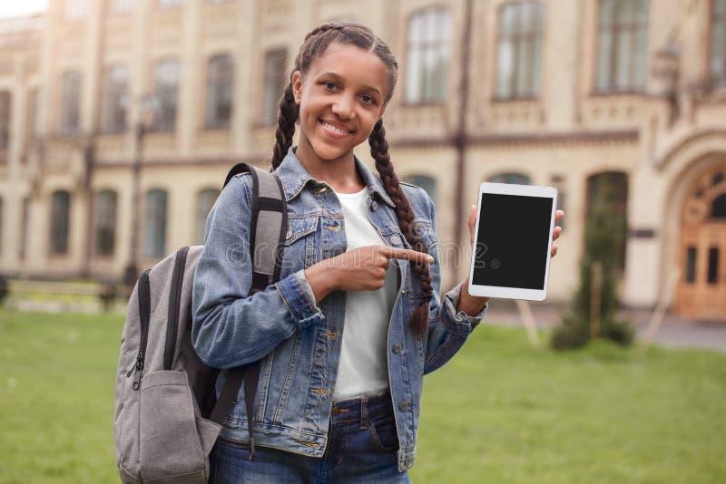 Młoda uczennica wskazuje przy ekranem cyfrowej pastylki przyglądająca kamera w cajgach z plecak pozycją przy szkolnym jardem zdjęcie royalty free