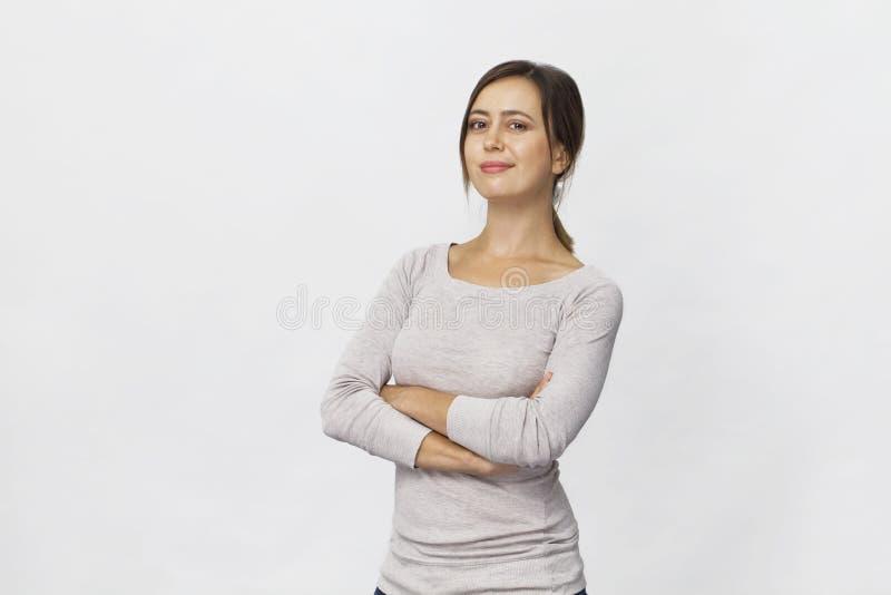 Młoda ufna brunetki kobieta uśmiecha się portrai z krzyżować rękami zdjęcie stock