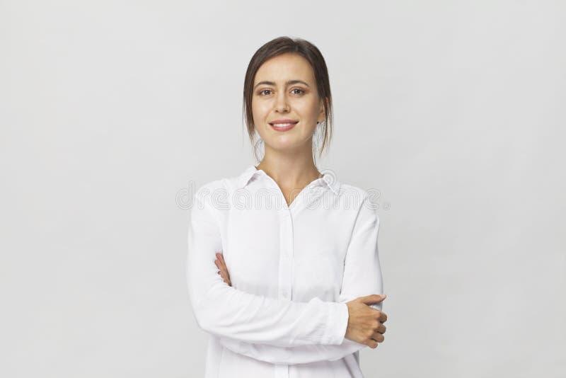 Młoda ufna brunetki kobieta w białym eleganckim koszulowym uśmiechniętym po zdjęcie stock