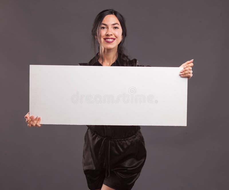 Młoda ufna kobieta pokazuje prezentację, wskazuje na plakacie zdjęcie royalty free