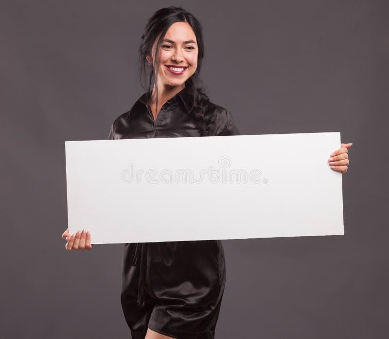 Młoda ufna kobieta pokazuje prezentację, wskazuje na plakacie obrazy royalty free