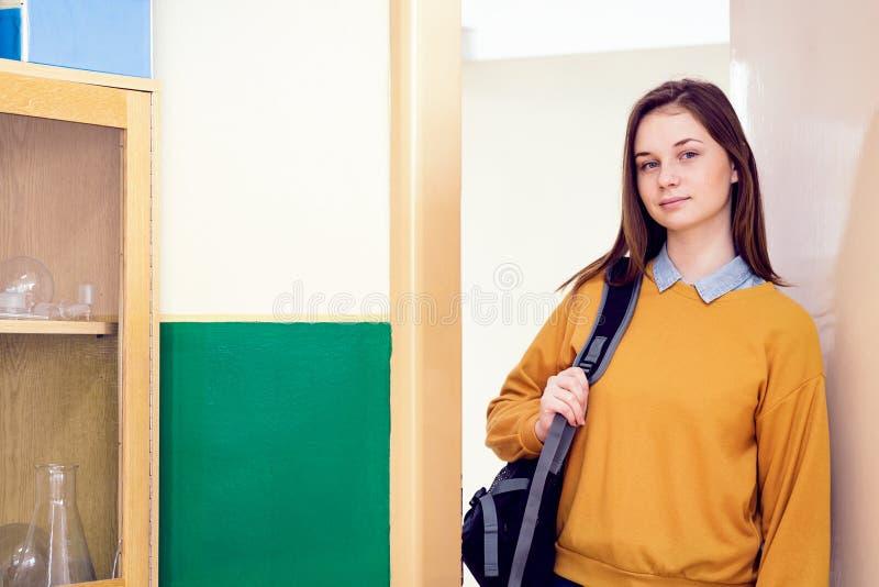 Młoda ufna uśmiechnięta żeńska student collegu pozycja w drzwi przy jej szkolnym, będący ubranym plecaka zdjęcia royalty free