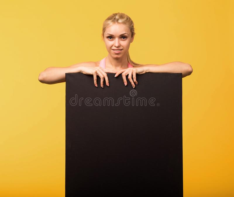 Młoda uradowana kobieta pokazuje prezentację, wskazuje na plakacie zdjęcia royalty free