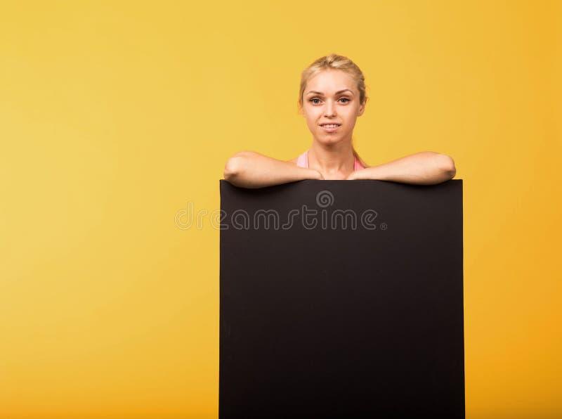 Młoda uradowana kobieta pokazuje prezentację, wskazuje na plakacie zdjęcie royalty free