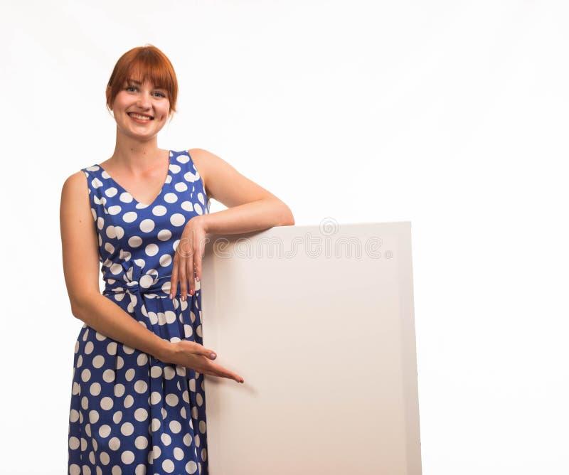 Młoda uradowana kobieta pokazuje prezentację, wskazuje na plakacie fotografia royalty free