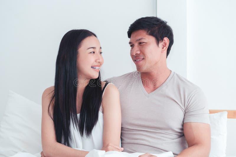 Młoda urocza para w łóżkowym uśmiechu i patrzeć each inny zdjęcia stock